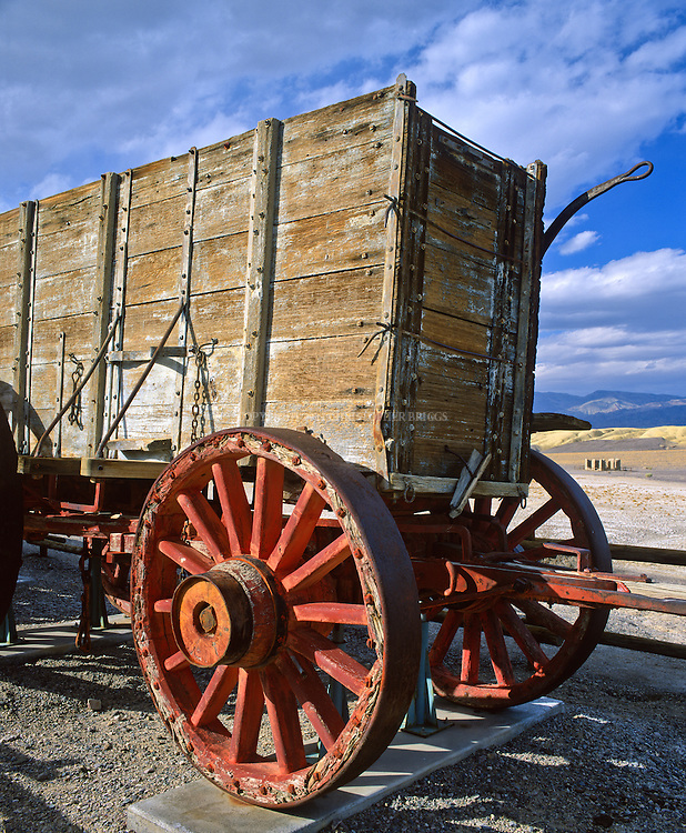 Twenty-mule team wagon on display at Harmony Borax Works.  Twenty-mule-team wagons among the largest ever pulled by draft animals, designed to carry 10 short tons (9 metric tons) of borax ore at a time. Rear wheels measured seven feet (2.1 m) high, tires made of one-inch-thick (25 mm) iron. Wagon beds measured 16 feet long and were 6 feet deep (4.9 m long, 1.8 m deep); constructed of solid oak, weighed 7,800 pounds (3,500 kg) empty; loaded with ore total weight of the mule train was 73,200 pounds (33.2 metric tons or 36.6 short tons). All hauled the entire 165-mile (275km) journey across the desert to the nearest railroad spur in Mojave. Teams hauled more than 20 million pounds (9,000 metric tons) of borax out of Death Valley in the six years of the operation. Death Valley National Monument Est. February 11, 1933. Est. as Death Valley National Park in 1994; 5,270 square miles (13,649 km2). Inyo County, CA.