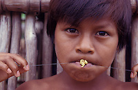 Gold mining inside Tukano Indigenous People territory at extracting Serra do Traira, border between Brazil and Colombia, Amazon rain forest. Native boy plays with a gold piece.