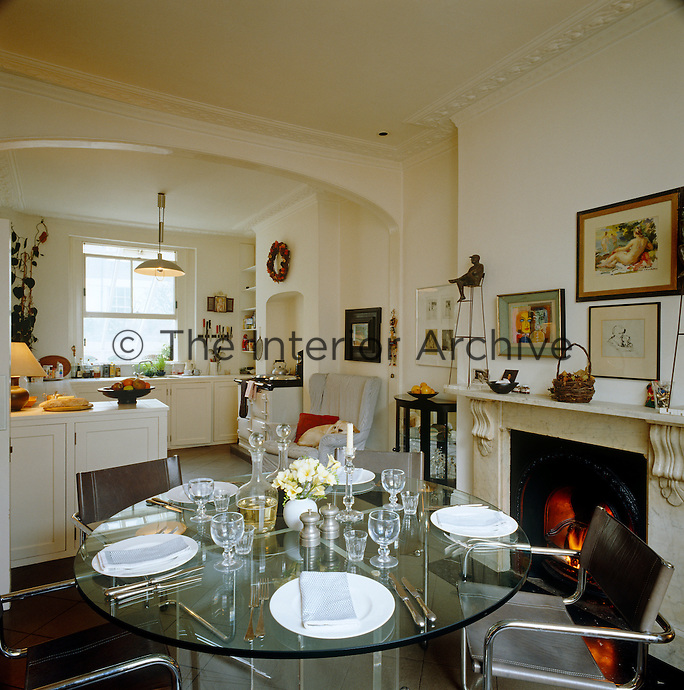 In this cosy kitchen-diner there is an Aga as well as an open fire whilst a contemporary note is struck with an elegant glass dining table and leather chairs