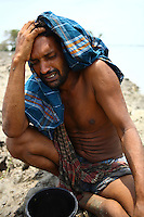 A man grieves as he sits on land washed away by Cyclone Aila. Thousands of people were displaced in Shyamnagar Upazila, Satkhira district after Cyclone Aila struck Bangladesh on 25/05/2009, triggering tidal surges and floods.