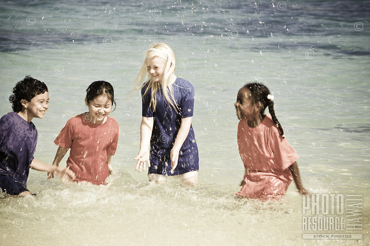 Ethnic mix of children playing at the beach in the water