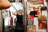 A customer tries on an authentic Flapper-style dress and 1930s hat, Glanz & Gloria vintage clothing store, Brunngasse, Bern, Switzerland, 27 August 2011
