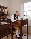 Corner of the Back Office, and Clerk's Desk in front of document cupboard and shelves. Costumed interpreter seated at the desk writing with quill and ink at Wordsworth House. M.R.