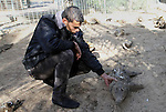 Palestinian worker inspects the dead animals in the zoo, in Khan Younis in the southern Gaza Strip, on January 31, 2015. The deaths of dozens of kinds of animals and birds in the garden of South Forest due to the Israeli aggression and the inability of the owner to reach her and look after her over 51 days due to the Israeli bombardment of the surroundings and the flight of the animals died from hunger and lack of interest and the owner estimated losses of millions of dollars, and died about 25 class and type of birds and animals. Photo by Abed Rahim Khatib