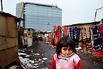 "THIS PHOTO IS AVAILABLE AS A PRINT OR FOR PERSONAL USE. CLICK ON ""ADD TO CART"" TO SEE PRICING OPTIONS.   A girl in an illegal Roma settlement in Belgrade, Serbia. The families that live here, many of whom survive from recycling cardboard and other materials, are under constant threat of eviction in order to make way for new high-rise office buildings."