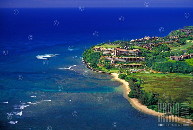 Aerial view of the Sheraton Hotel at Princeville, Kauai, with the coastline and ocean curving along the hotel area's edge.