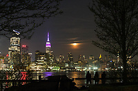 HOBOKEN, NJ - APRIL 11: People look at The Empire State Building lit purple and gray in honor of the 100th anniversary of the New York state police while moon rise over middle Manhattan as it is seen from the shore on April 11, 2017 in Hoboken, New Jersey. Since April 11, 1917, the State Police have been committed to helping New Yorkers by providing them with friendly, professional service. Photo by VIEWpress/Eduardo MunozAlvarez