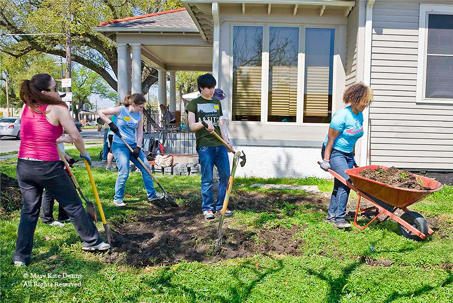 Young women and young man students dig with shovels and haul wheelbarrow in yard of New Orleans home in the 9th ward