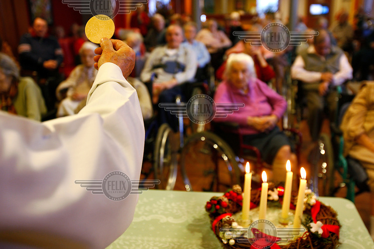 A priest holds out sacramental bread during Catholic mass in a home for elderly people.