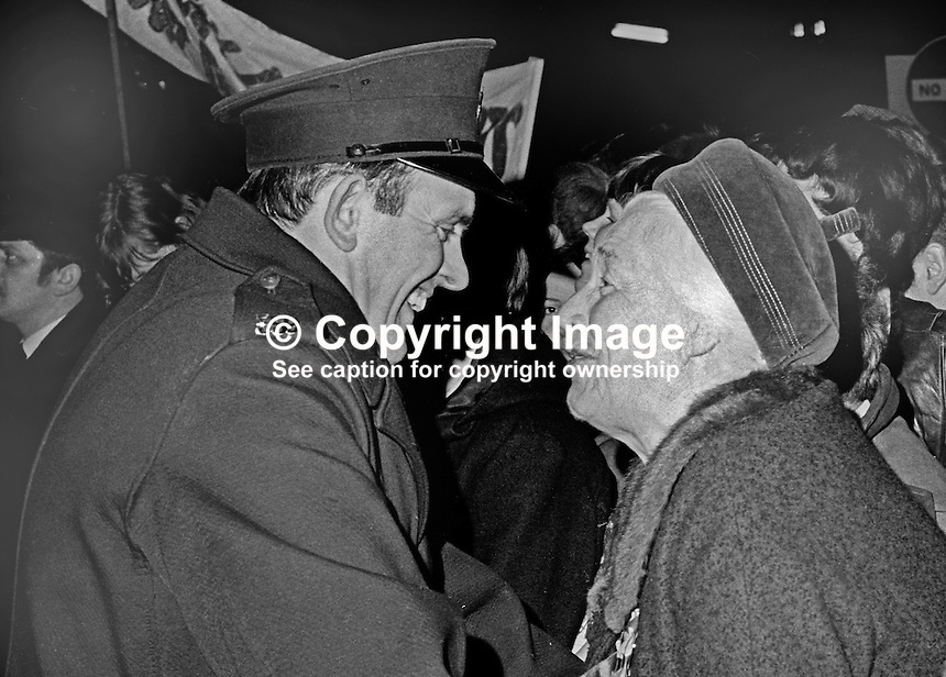 Mrs Isabella Paisley, mother of Rev Ian Paisley, fundamentalist preacher and loyalist politician, looking very happy at her son's breakthrough election victory in the April 1970 Bannside by-election. She is seen talking to a policeman outside the Town Hall where the count took place. Paisley taking the Bannside seat formerly held by Ulster Unionist Prime Minister Captain Terence O'Neill was a major politcal breakthrough for him. 16th April 1970. 197004160116a<br />