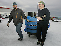 Saturday, Feb. 18, 2006  Anchorage, Alaska. Volunteer Iditarod Airforce pilots and others load straw into Cessna planes headed out to checkpoints along the trail.  Each musher is given one bale of straw at a checkpoint to bed their dogs down.