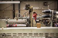 Un'operaia pensosa a una macchina per tessituta Bute tartan mills