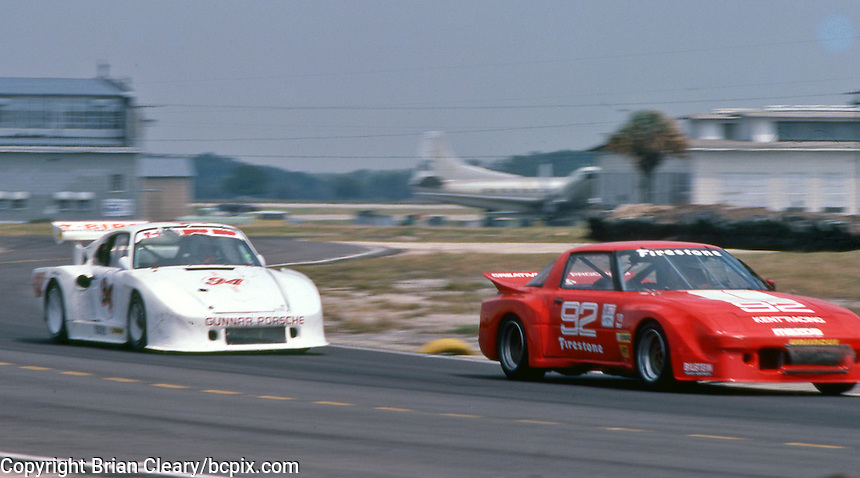 The #92 Mazda RX-7 of Lee Mueller and Terry Visger leads the #94 Porsche 935K3 of Bill Whittington and Don Whittington at  the 12 Hours of Sebring endurance sports car race, March 19, 1983.  (Photo by Brian Cleary/www.bcpix.com)