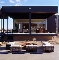 The layout of the house offers different areas for outdoor living with a large covered terrace and a patio with benches and a brazier