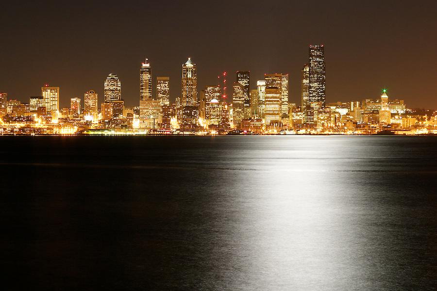 Seattle city skyline at night with light of full moon reflected in Elliot Bay , Seattle, Washington, USA