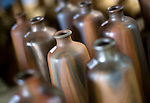 Vitrified earthenware flasks used to store specially brewed awamori line the shelves at the Chuko distillery in Naha, Okinawa Prefecture, Japan, on May 20, 2012. Photographer: Robert Gilhooly