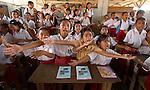 School girls enthusiastically sing during a Pride Campaign visit, Komodo Village, Komodo National Park