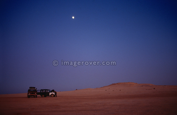 Africa, Algeria, Sahara Desert, nr. El Oued. Travellers, undertaking a sahara trip with their Series Land Rovers, servicing the vehicles under moonlight after a rough long days drive. --- No releases available, but release may not be required. Automotive trademarks are the property of the trademark holder, authorization may be needed for some uses.