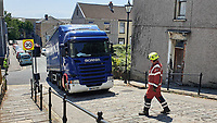 Pictured: A fireman makes sure that the David Hathaway articulated lorry which became stuck, reverses safely down Constitution Hill, Wales, UK. Monday 15 July 2019<br /> Re: An articulated lorry that got stuck in Swansea's steepest road, had to be towed away.<br /> The David Hathaway vehicle was attempting to turn from Brooklands Terrace to Constitution Hill just after 11am but successive attempts by the driver proved difficult as the wheels kept losing traction.<br /> Police, a fire service vehicle and a recovery truck attended which helped free the lorry.
