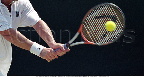 Tennis detail showing the hands and arms as a male player strikes the ball with his racquet, Wimbledon Tennis Championships, 990702. Photo: Matthew Clarke/Action Plus....1999.racket rackets racquets.  detail.sports equipment. s.  ident.ball.hand hands grip grips.closeup close up close-up.illustration