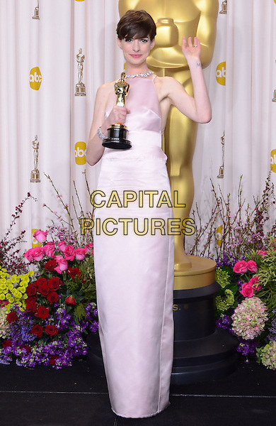 Anne Hathaway (wearing Prada).85th Annual Academy Awards held at the Dolby Theatre at Hollywood & Highland Center, Hollywood, California, USA..February 24th, 2013.pressroom oscars full length pink sleeveless silk satin dress award trophy winner hand arm waving .CAP/ADM/RE.©Russ Elliot/AdMedia/Capital Pictures.