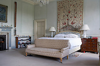 An upholstered sofa stands at the foot of the bed in the master bedroom