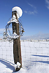 Rustic fence post  with a coil of barbed wire covered in snow