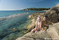 Young girls on the rocky lakeshore after swimming