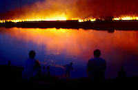 Afrikaners watch as a burning wheat field is reflected in the Orange River, in Orania, an all white community in Northern Cape Province, South Africa. (Photo by: Per-Anders Pettersson)