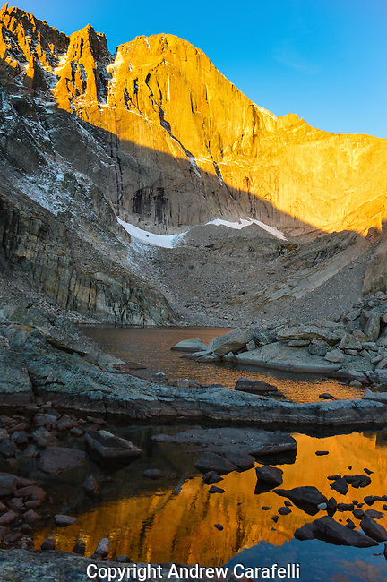 The 2000 foot East Face of 14,255 foot high Long's Peak, illuminated  by the rising sun, reflects in Chasm Lake sitting below at 11.823 feet in Rocky Mountain National Park, Colorado.