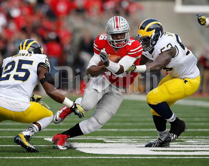 Ohio State Buckeyes quarterback J.T. Barrett (16) runs between Michigan Wolverines defensive end Mario Ojemudia (53) and defensive back Dymonte Thomas (25) during the first quarter of the NCAA football game at Ohio Stadium on Nov. 29, 2014. The Buckeyes won 42-28. (Adam Cairns / The Columbus Dispatch)