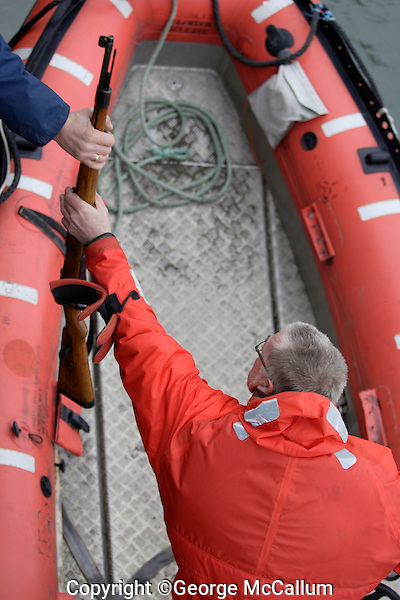 Tourist Guide in zodiac taking rifle for protection against Polar bears on Spitzbergen Svalbard, Arctic Norway