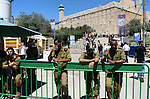 Israeli policemen stand guard as Jews walk outside the Tomb of the Patriarchs during the Jewish Passover holiday, in the West Bank city of Hebron, April 5, 2015. Due to the haste with which the Jews left Egypt some 3,500 years ago, the bread they had prepared for the journey did not have time to rise, therefore to commemorate their ancestors' plight, religious Jews do not eat leavened food products throughout the eight-day Pesach holiday. Photo by Mamoun Wazwaz
