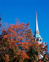 The steeple of the Amherst Congregational Church rises into the clear blue sky beyond a tree bearing fall foliage. New Hampshire.