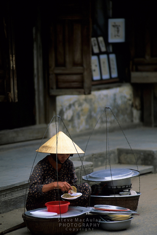 Woman preparing her mobile kitchen for the lunch rush, Hoi An, Vietnam