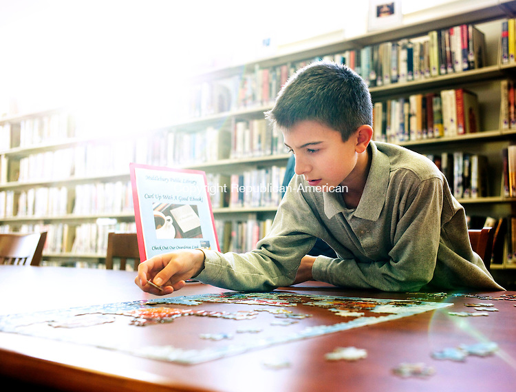 Middlebury, CT- 25 November 2015-112515CM03-  Nathaniel Zembruski, 12, left, of Naugatuck works on a puzzle at the Middlebury Public library on Tuesday.  Zembruski was working on a puzzle with his grandfather Nick Corsi of Middlebury.  A calendar of events for the month of December is available at the library.  For more information stop by the library located at 30 Crest Road or contact them by phone at 203-758-2634. Christopher Massa Republican-American