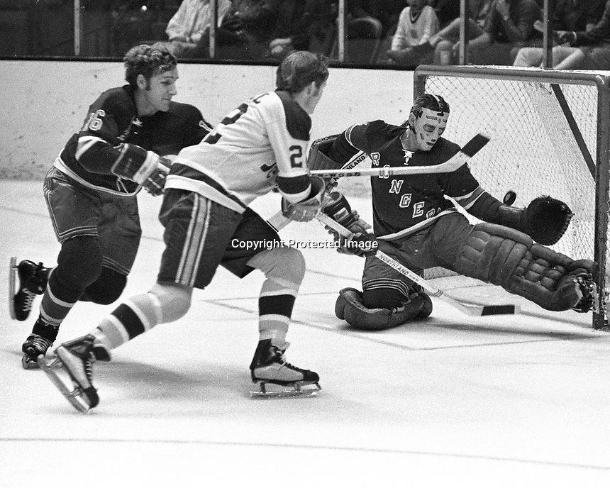 Seals vs NY Rangers: Seal Dennis Hextall takes a shot at Ranger goalie Ed Giacomin, and Rod Seiling. .(1970 photo by Ron Riesterer)