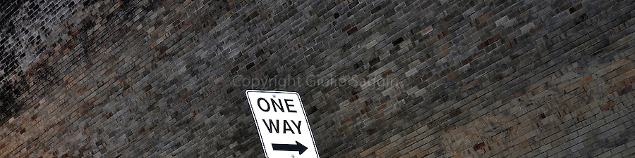 A One Way street sign stands next to a brick wall in a back street in the north shore of Sydney suburb of Mosman.