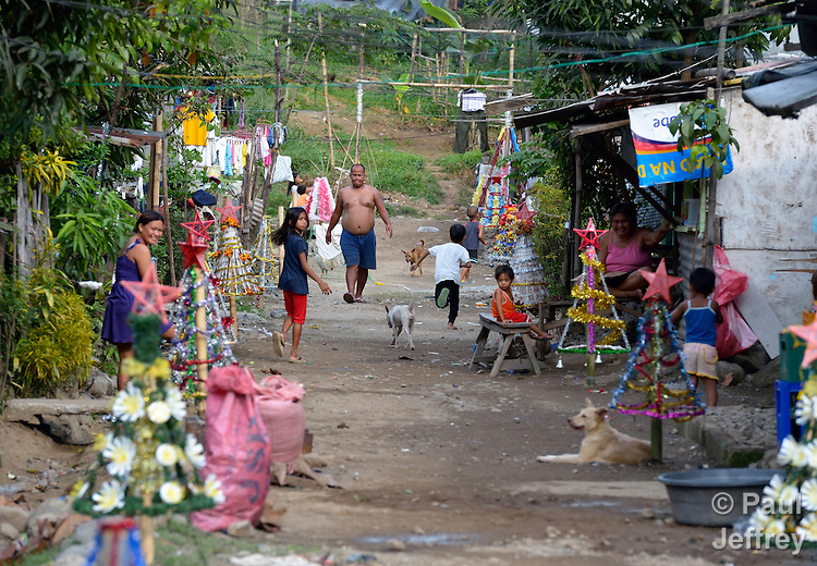 A street scene in the Suburban neighborhood of Rodriguez, Rizal, in the Philippines. Most of the community's families were relocated here from other area of Manila and the nearby countryside to make way for urban renewal projects or to move them out of harm's way. Yet the new community was hit hard by Typhoon Ketsana in 2009, and Christian Aid, a member of the ACT Alliance, provided emergency relief supplies. Over the years since, with help from Christian Aid and other groups, community members have organized themselves and engaged in a process of disaster risk reduction, including identifying and mapping high-risk zones and evacuation routes in their area. Christian Aid has also assisted with financial and technical support for income generating livelihood projects and community enterprises.