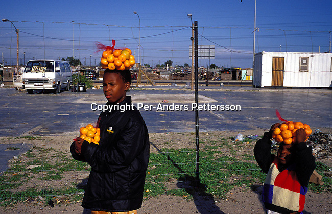 ditown00183 Digital. Township  Unidentified girls carrying oranges on their heads outside Nonqubela train station on August 11, 2001 in Site B Khayelitsha, a township about 35 kilometers outside Cape Town, South Africa. Khayelitsha is one of the poorest and fastest growing townships in South Africa. People usually come from the rural areas in Eastern Cape province to find work as maids and laborers. Most people don't find work and the unemployment rate is very high, together with lot of violence and a growing HIV-Aids epidemic itÕs a harsh area to live in. Vendor, electricity, taxi.©Per-Anders Pettersson/iAfrika Photos.