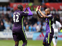 SWANSEA, WALES - MAY 17: (L-R) Yaya Toure of Manchester City celebrates his second goal with team mate Fernandinho, making the score 3-2 to his team during the Premier League match between Swansea City and Manchester City at The Liberty Stadium on May 17, 2015 in Swansea, Wales. (photo by Athena Pictures/Getty Images)
