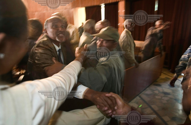 Chaotic scenes in court at the end of the long genocide trial of Mengistu Haile Mariam, former dictator of Ethiopia. Relatives of some of the 73 defendants (only 33 of whom were in court) try to greet them but are prevented by guards. Mengistu, one of those absent, living in exile, was sentenced to life imprisonment. His Derg regime, in power from 1974 to 1991, is accused of killing tens of thousands of people in what became known as the Red Terror.