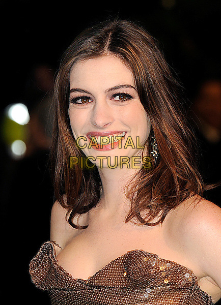 ANNE HATHAWAY .Royal World Film Premiere of 'Alice in Wonderland' at the Odeon cinema, Leicester Square, London, England, UK, 25th February 2010 .arrivals portrait headshot make-up strapless brown sequined sequin strapless bronze eyelashes earrings dangly smiling .CAP/BEL.©Tom Belcher/Capital Pictures.