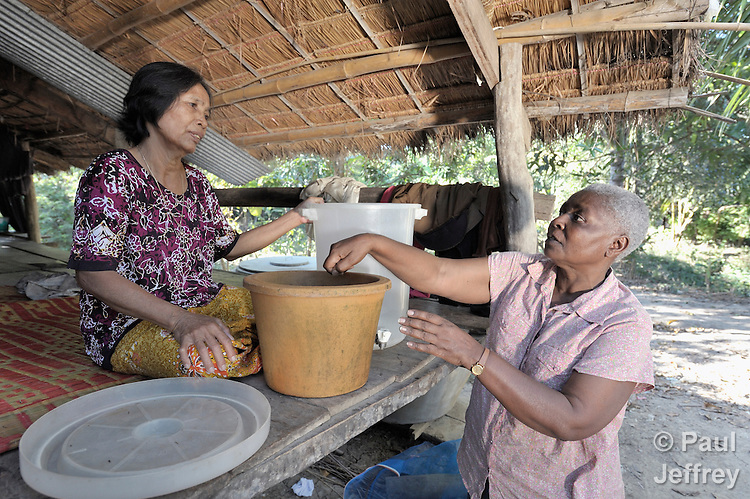 Irene Mparutsa, right, a United Methodist missionary, discusses the proper use of a water filter with Hach Ath in the Cambodian village of Talom. Mparutsa works with the Community Health and Agricultural Development program of the Methodist Mission in Cambodia.