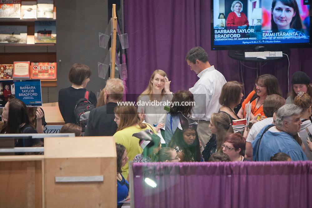 HSKU 20140531 United Stated, New York. Book Expo America, Javits Center. Finnish author Emmi Itaranta signs ebook copies of her novel in English. Photographer: David Brabyn