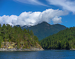 British Columbia, Canada: View of cloud wrapped mountains above the calm waters of Homfray Channel, Desolation Sound