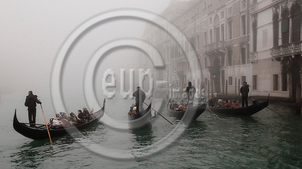 Venice-Italy - January 16, 2011 -- A group of gondolieri / gondoliers on tour with tourists on Grand Canal / Canal Grande in the early morning winter mist, gondola -- tourism, infrastructure, transport, water -- Photo: Horst Wagner / eup-images