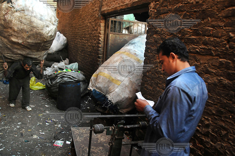 A man carries a huge sack of plastic, collected from throughout Cairo and destined for recycling by the Zaballeen, a minority group of Coptic Christians who have worked as Cairo's informal rubbish collectors for the past 70 to 80 years.