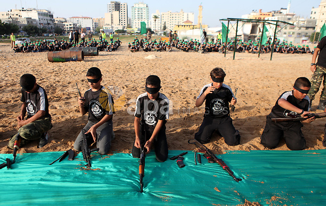 Palestinian youths demonstrate their skills during a graduation ceremony of a military-style summer camp organized by the Hamas movement in Gaza City June 19, 2014. Hamas stages dozens of military-style summer camps for young Palestinians in the Gaza strip to prepare them to confront any possible Israeli attack, organisers said. Photo by Ezz Zanoun