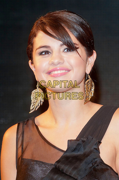"Selena Gomez .At HMV, Oxford Street, London, England..for a signing to session to launch her new album, ""When The Sun Goes Down""  .July 5th 2011.headshot portrait black sheer dangling gold earring.CAP/HT.©Hugh Thompson/Capital Pictures."